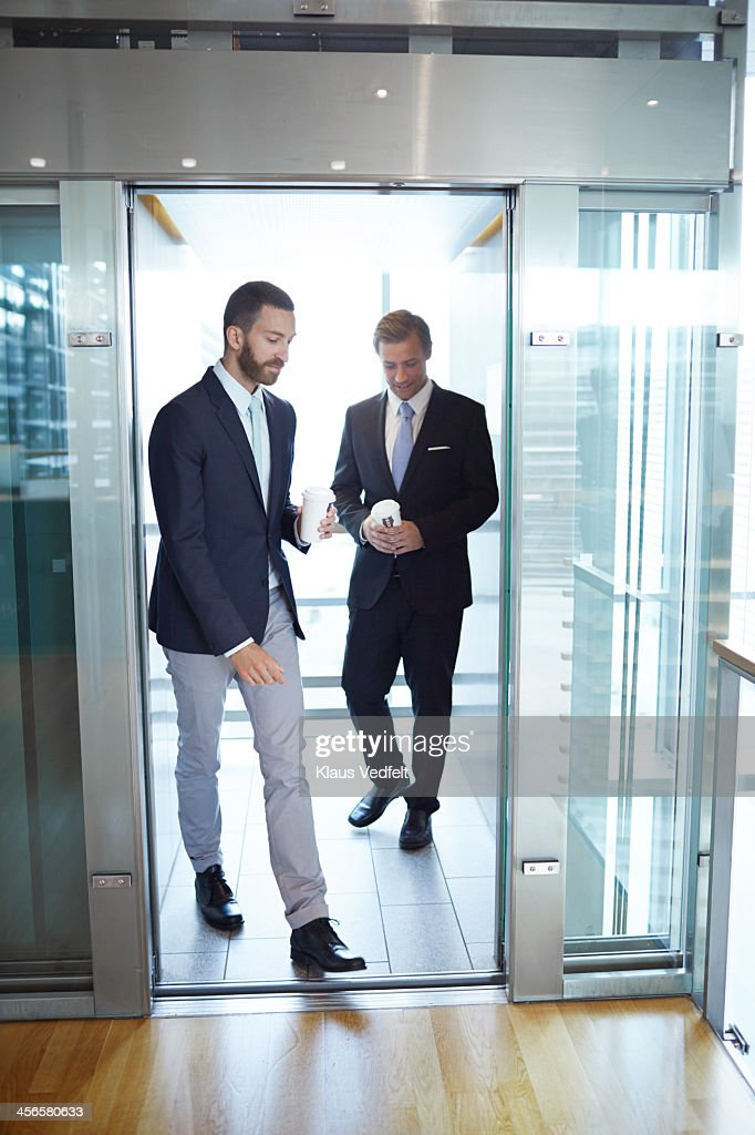 Business people walking out of elevator : Stock Photo