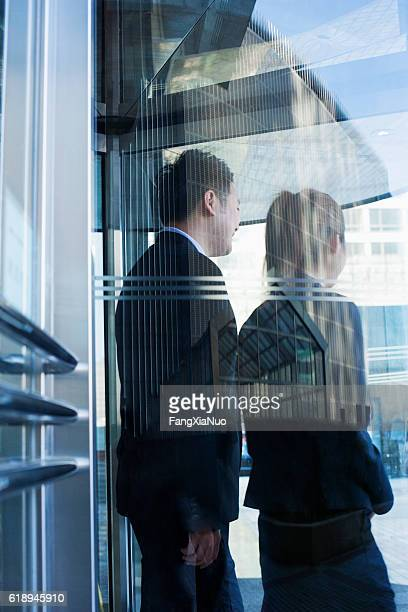Business people walking out of glass door