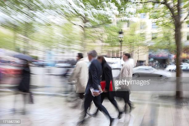 Gens d'affaires marchant dans la rue de la pluie, mouvement flou, Paris, France