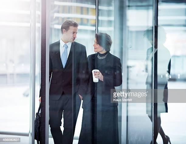 Business people walking threw swing door