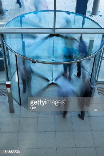ビジネスの人々を歩く回転ドアのガラス