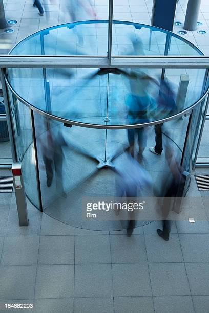 Business People Walking Through Glass Revolving Door