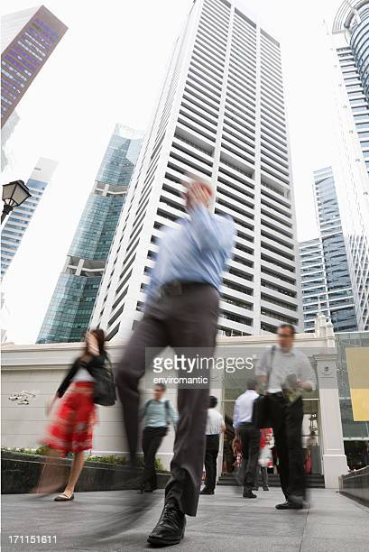 Business people walking through Singapore's financial district.