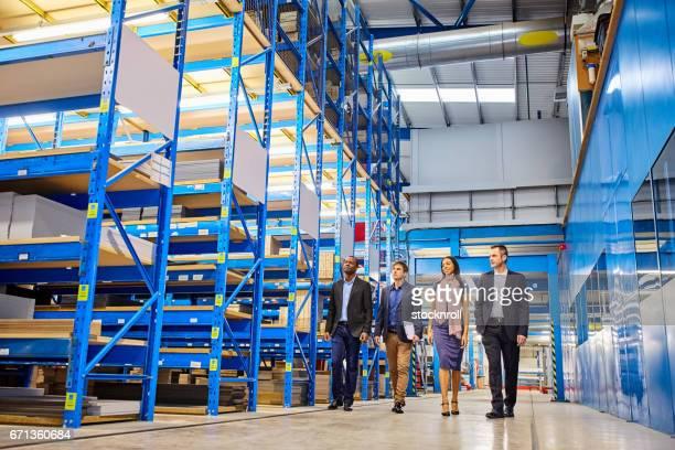 Business people walking through warehouse