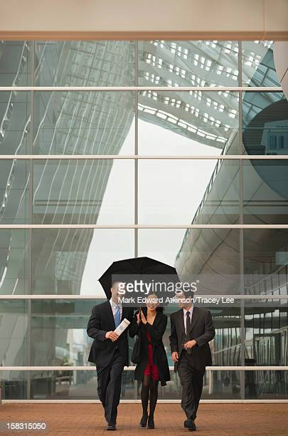 Business people walking together with umbrella