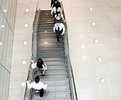 Business people walking up and down stairs