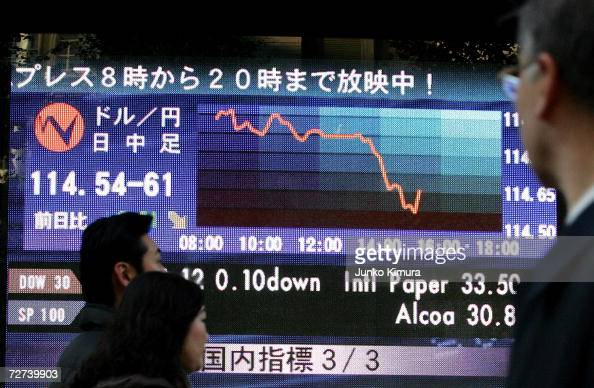 Business people watch an electric board indicating the foreign currency of 1145962 yen against the US dollar at a foreign exchange brokers on...