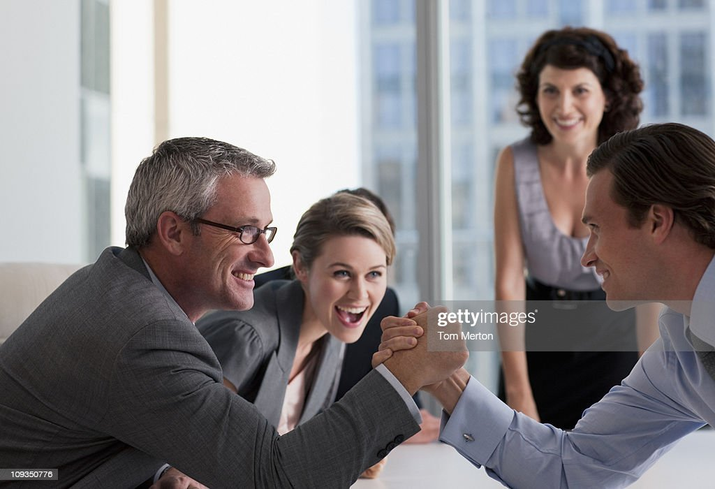 Business people watching businessman arm wrestling : Stock Photo