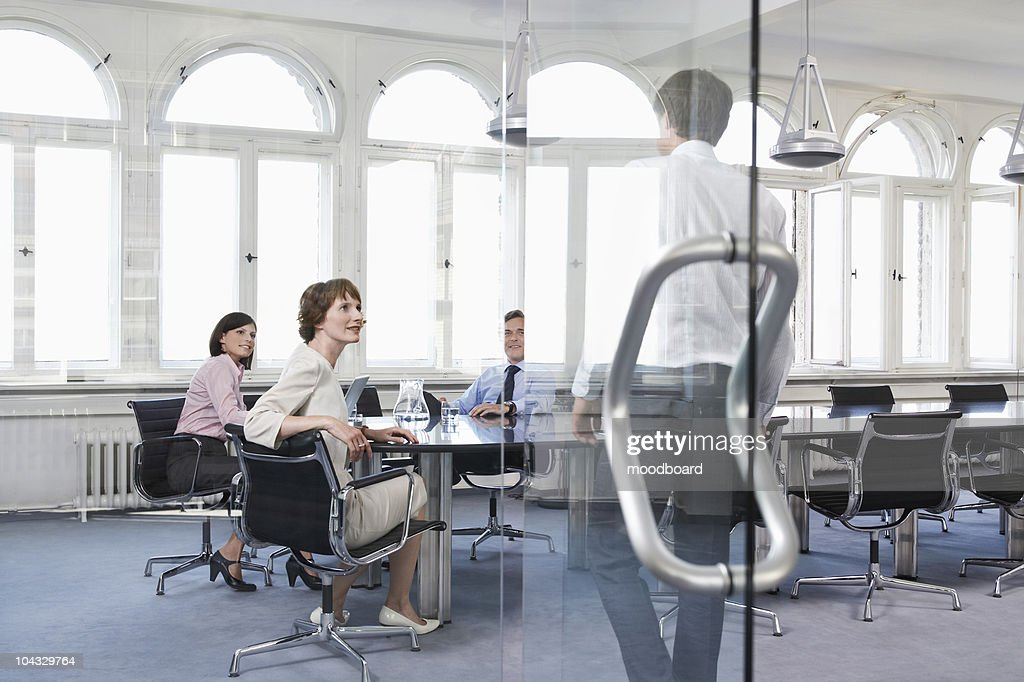 Business people watching colleague entering office : Stock Photo