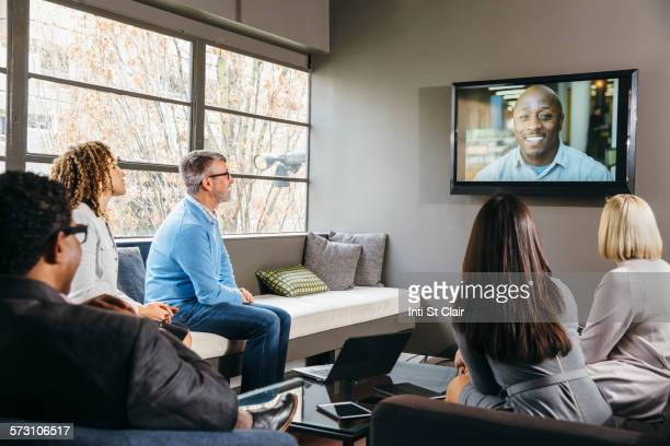 Business people watching teleconference in office meeting