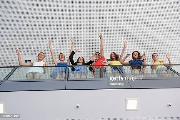 Business people waving from balcony