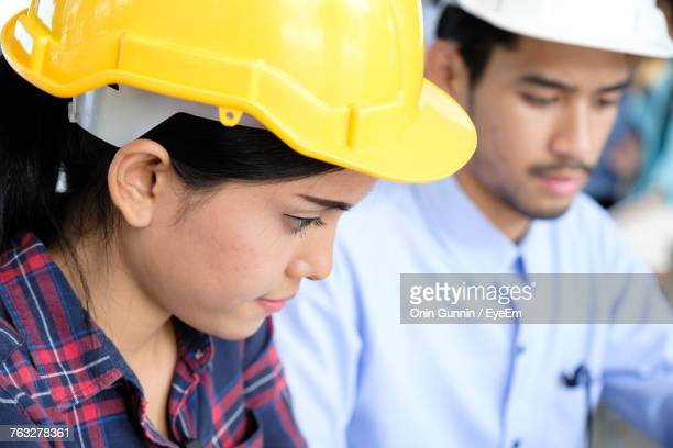 Business People Wearing Hardhats While Looking Down In Office