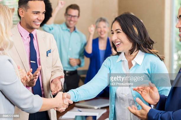 Business people welcome new employee during staff meeting