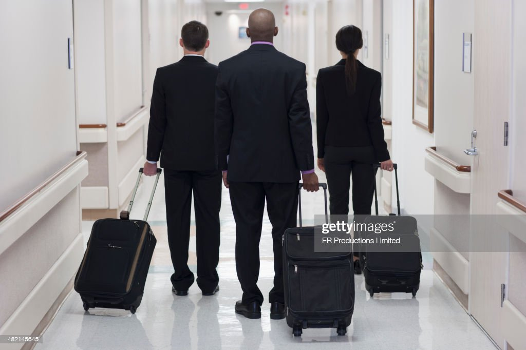Business people wheeling luggage in hospital