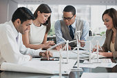 Business people with blueprints and wind turbine models