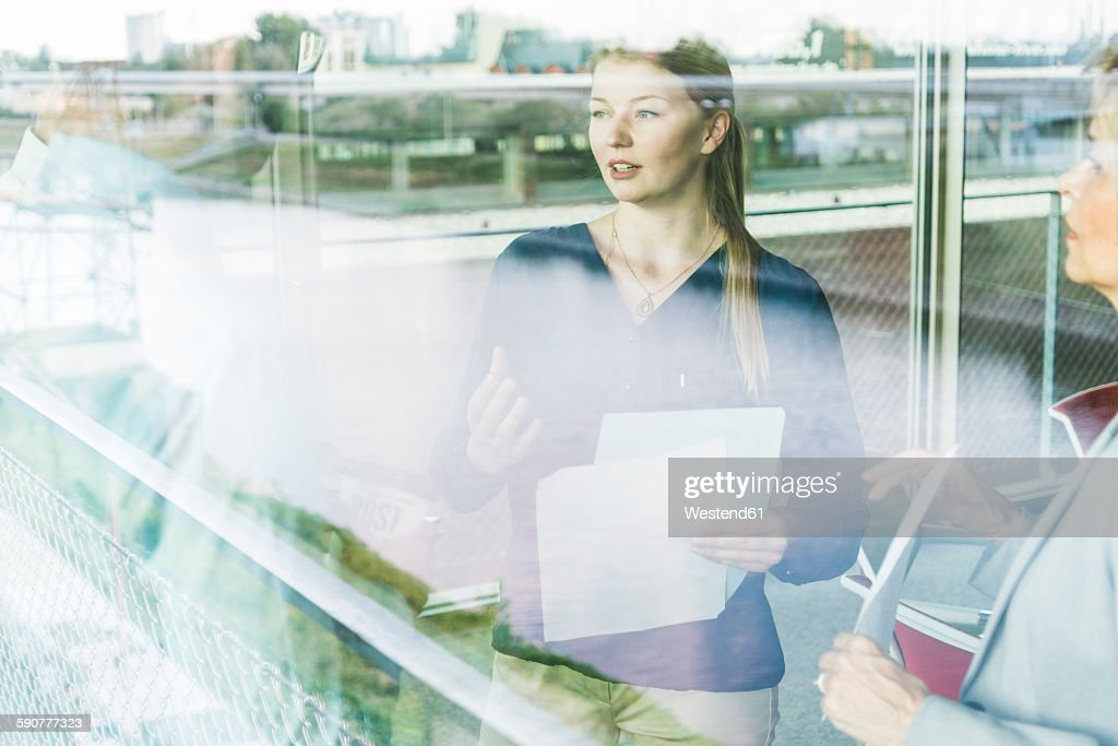 Business people with documents talking behind window pane