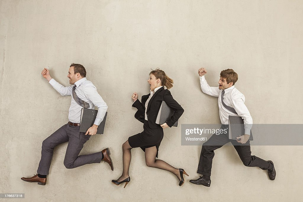 Business people with files running behind each other
