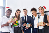 happy young multiethnic business people holding gifts and smiling at camera in office