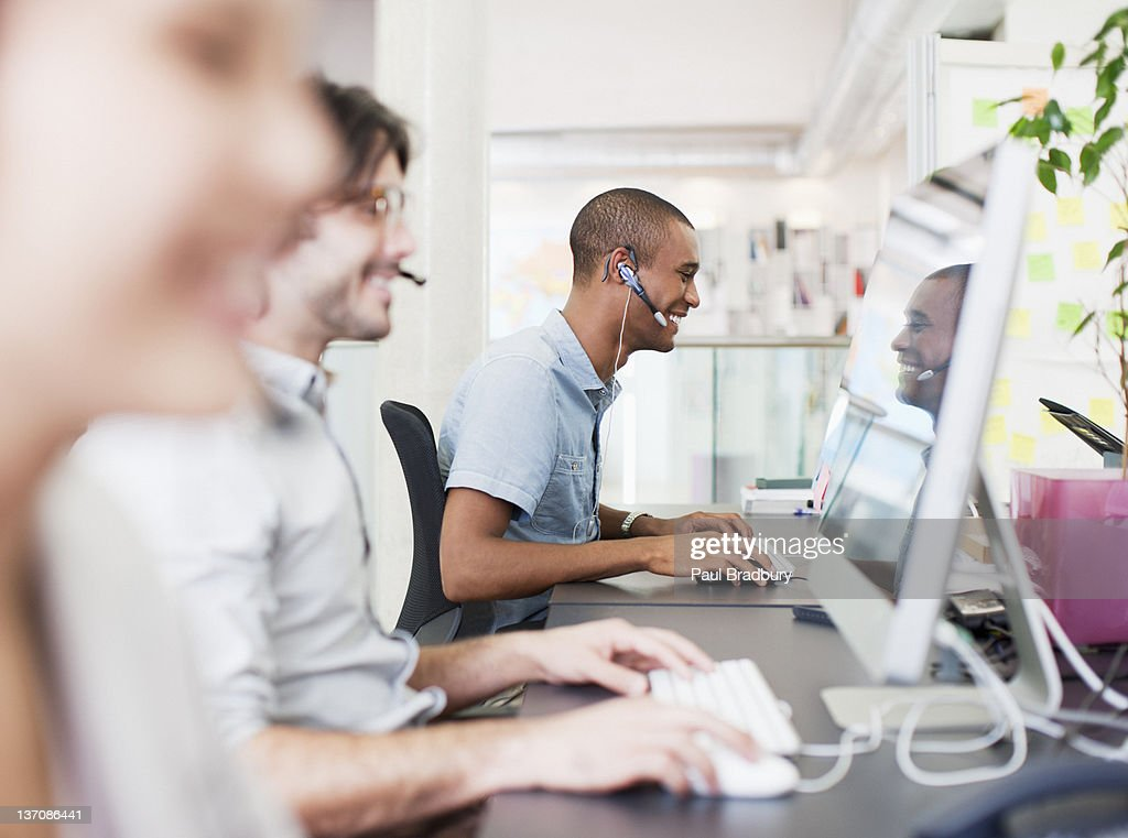 Business people with headsets working at computers in office : Stock Photo