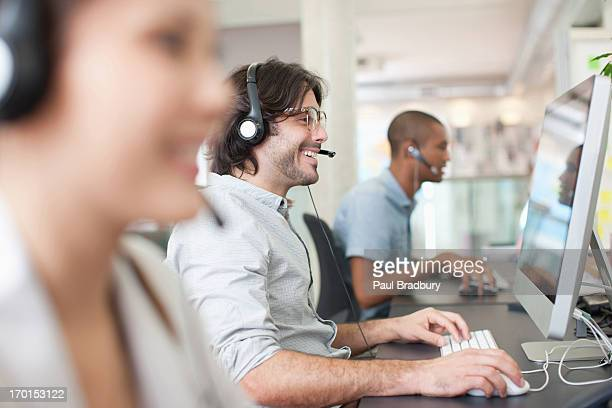 Pessoas de negócios com auscultadores trabalhando em computadores no escritório
