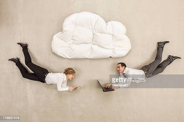 Business people with laptop and mobile phone below cloud shape pillow