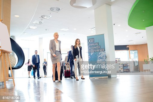 Business people with luggage walking in convention center : Stock Photo