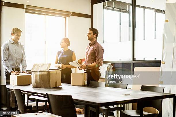 Business people with packing boxes in board room