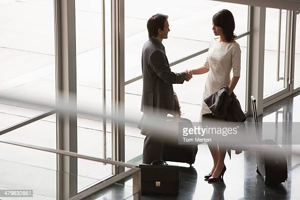 Business people with suitcases greeting one another