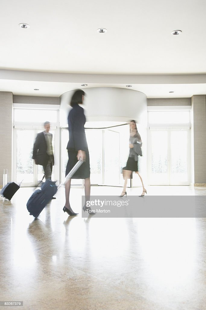 Business people with suitcases walking in lobby : Stock Photo