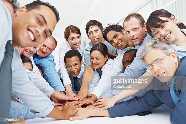 Business people with their hands together showing unity