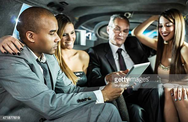 Business people with young women in a limousine.