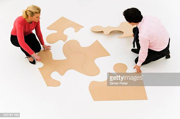 Business people work at finishing puzzle