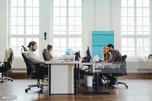 Business people working at desks in creating workspace