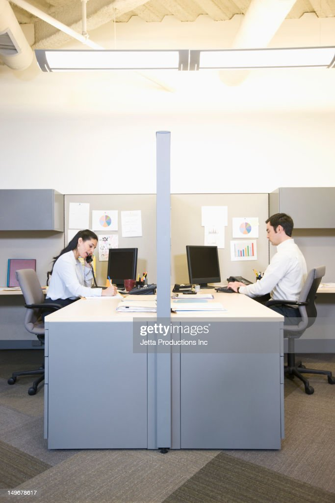 Business people working at desks in cubicles