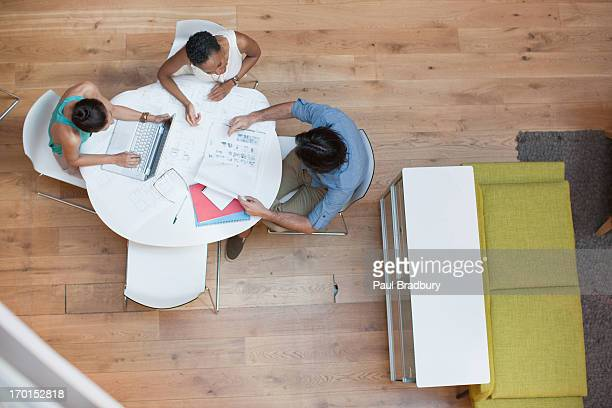 Business people working at table with laptop and paperwork