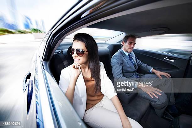 Las personas de negocios trabajan en backseat of car