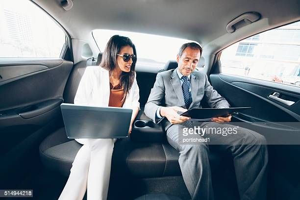 Business people working in backseat of car