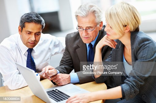 Business people working on a laptop at board meeting : Stock Photo