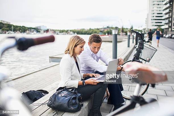 Business people working on laptop against clear sky