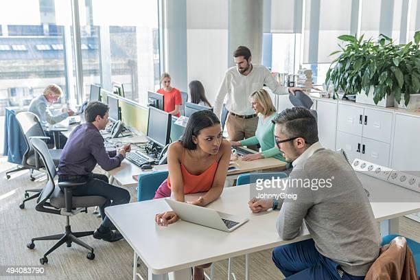 Hommes d'affaires travaillant sur ordinateur portable dans un bureau moderne