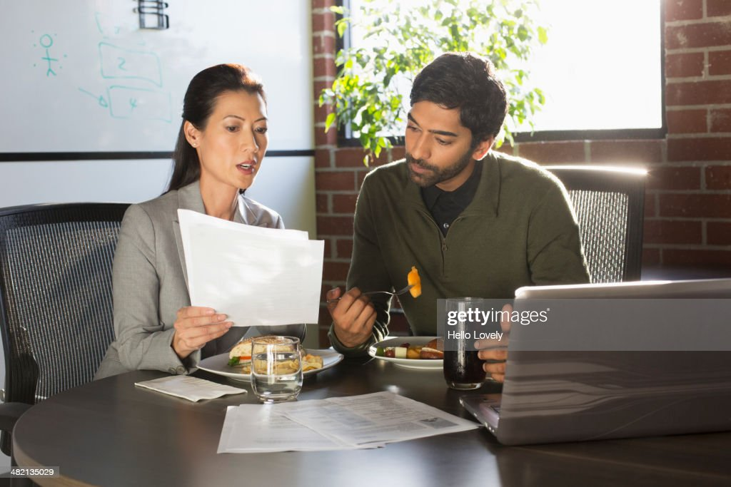Business people working over lunch : Stock Photo