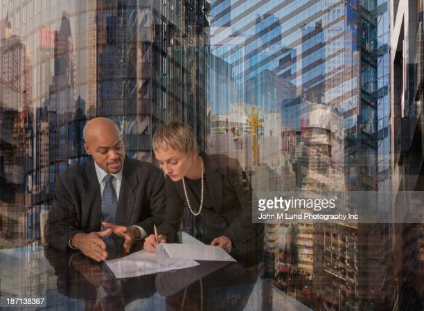 Business people working over skyscrapers