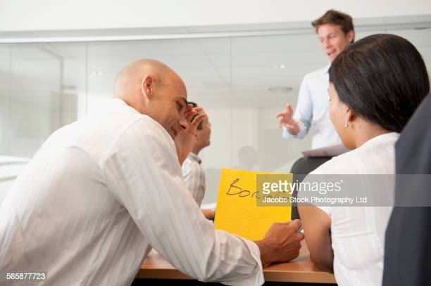 Business people writing bored in office meeting
