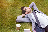 business person having break, laying in park.