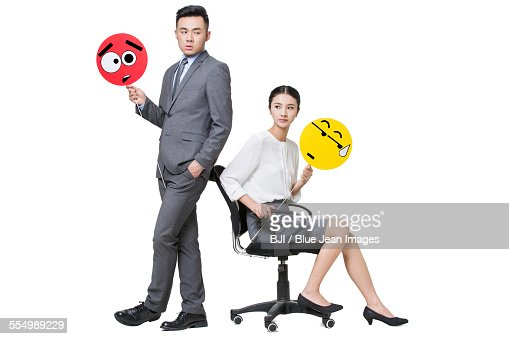 Business person holding embarrassed emoticon faces