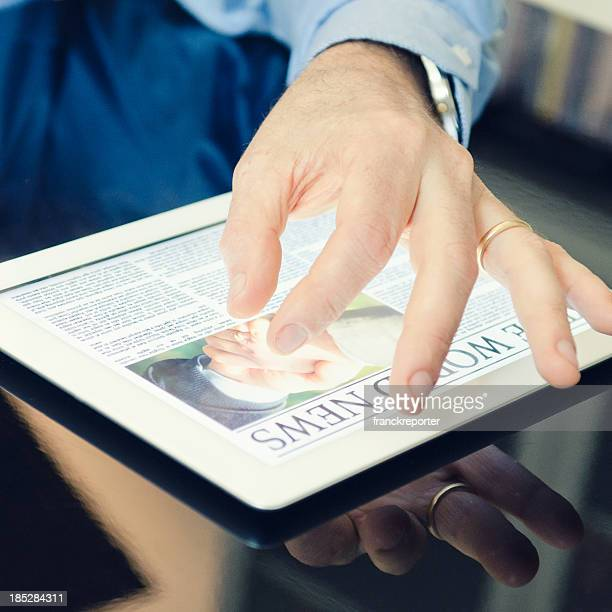 Business person reading a newspaper on digital tablet