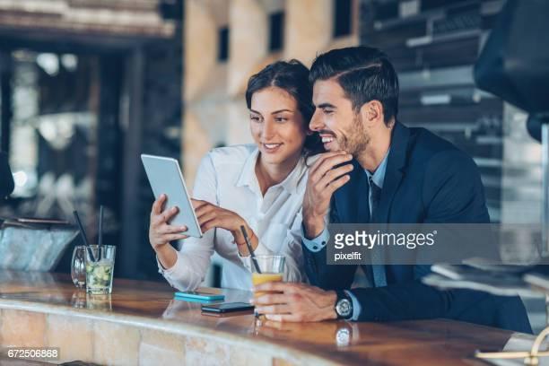 Affärspersoner med digital tablett och drycker i hotellets lobby