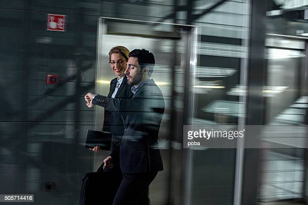 Business professionals passing through office building lobby