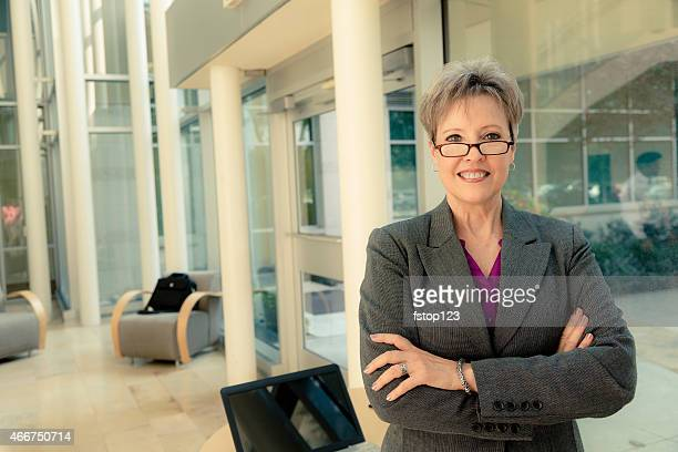 Business:  Senior businesswoman in modern office lobby.