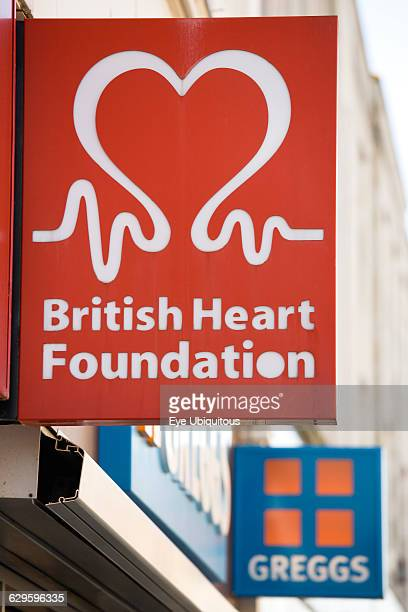 Business Shops Charity British Heart Foundation sign on a high street shop with a Greggs pie shop sign beyond it